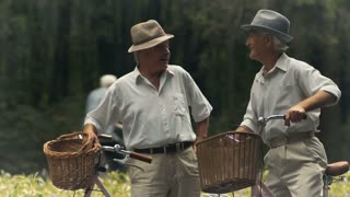 Two elderly friends with bicycles are talking in the park
