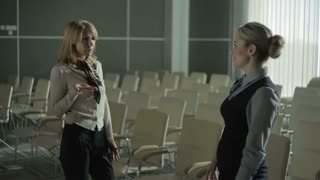 Two females talking in the conference hall of the airport