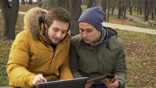 Two friends students uses laptop and tablet outdoors