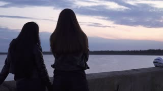 Two girls bikers in leather jackets enjoy beautiful evening view at the sea