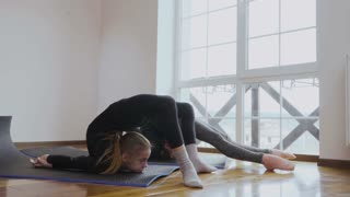 Two girls makes a stretching exercises in the room at home