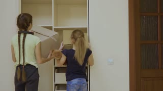 Two girls put their things into a cupboard after the relocation in a new house