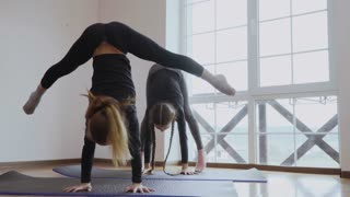 Two girls stands on hands and makes an air split upside down