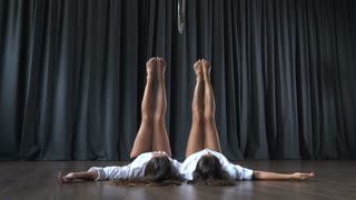 Two girls warms up on floor before making tricks on the aerial hoop