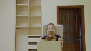 Two happy girls with boxes relocates in a new house