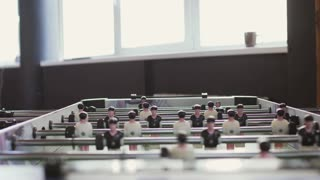 Two males plays table soccer