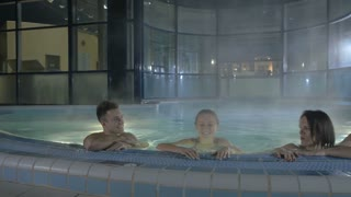 Two men and two girls are swimming in the pool after the sauna