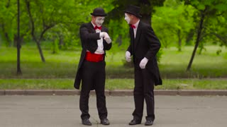 Two mimes do performance in the park