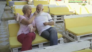 Two old love people eats popcorn in summer cinema