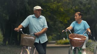 Two old people with bicycles talks in park