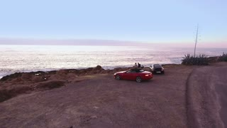 Two people relax near the ocean after traveling on cars