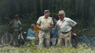 Two pleasant old men are dancing in the park