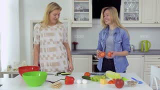 Two smiling girlfriends cokking fresh salad together and have fun at the kitchen