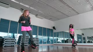 Two sporty women jumping in kangoo shoes in the dance studio