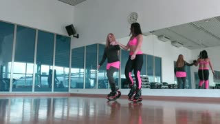Two women jumping in kangoo shoes in the gym