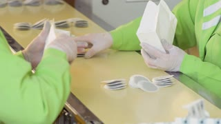 Two workers are packing tea bags into packages for sale