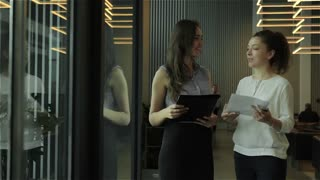 Two young businesswomen talking in lobby in office center