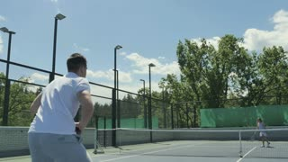 Two young friends plays tennis at the tennis court outdoors