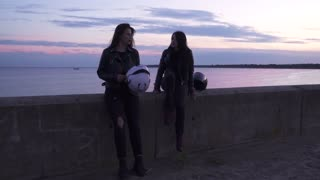 Two young girls bikers relaxing at evening embankment