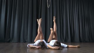 Two young girls lays on floor and stretches before making tricks on aerial hoop