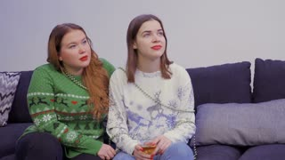 Two young girls sits on sofa at home and listens someone outside the camera