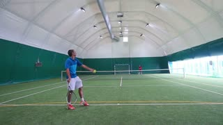 Two young guys playing tennis on court in slowmotion
