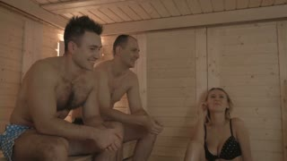 Two young men and girls relaxing in the sauna