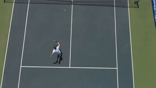 Two young people play tennis at the tennis court outdoors
