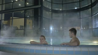 Two young people relax in swimming pool
