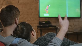 Two young people watching football on TV