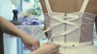 Tying a white corset on beautiful dress