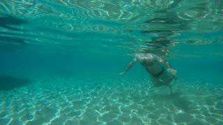 Underwater - fat man swims in blue water