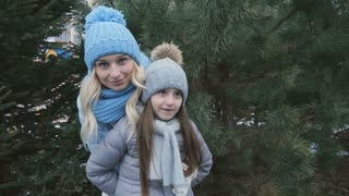 Сute mother and daughter with presents at the fir-tree background