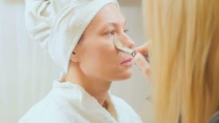 Visagiste doing makeup to young woman