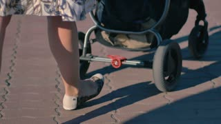 Walking mother's legs with baby carriage