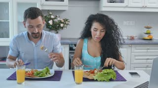 Wife and husband have a breakfast, the woman talks on the phone