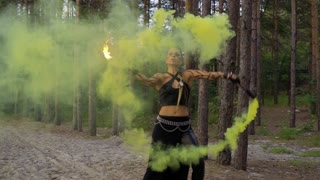 Wild looking woman is dancing with fire stick and smoke bomb