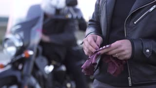 Woman biker put on hands the biker leather gloves