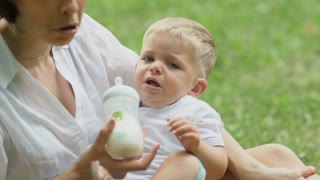 Woman calms her son and give him a milk
