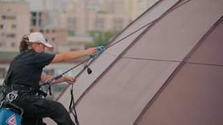 Woman climber climbs at the dome roof when it rains