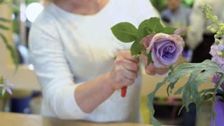 Woman cut roses and make flower composition