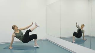 Woman does sit ups at the mat