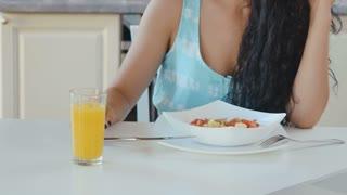 Woman drinks an orange juice during breakfast