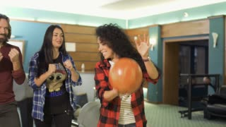 Woman high-fiving to her friends after throwing a bowling ball