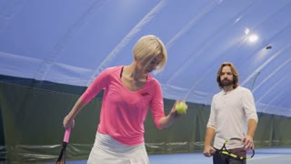 Woman hit tennis ball and man shows thumb up after her hit