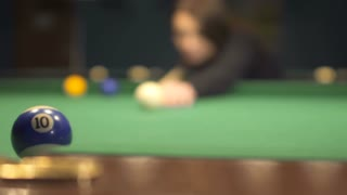 Woman hit the ball into a pocket in billiard