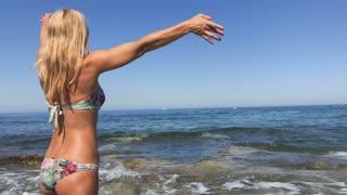 Woman in bikini waves hands standing on the seashore