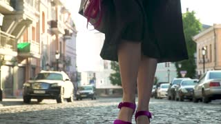 Woman in black dress and in purple shoes on high heels is walking in slow motion