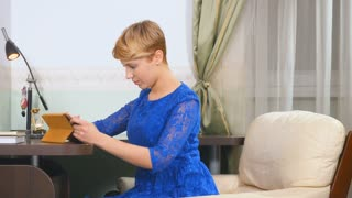 Woman in blue dress uses tablet