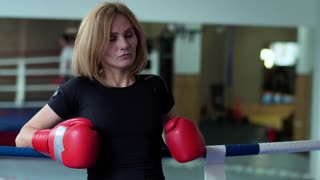Woman in boxing gloves leans at ropes of boxing ring